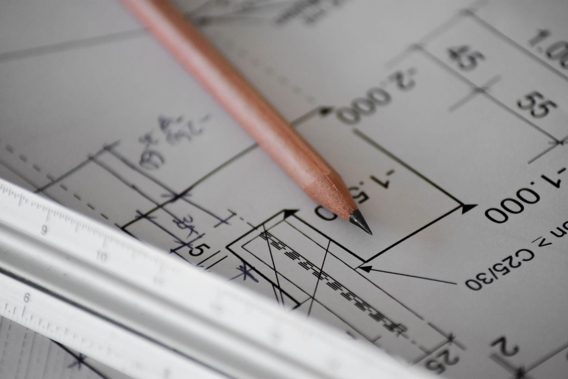 Bleistift liegt auf dem Grundriss eines Hauses.